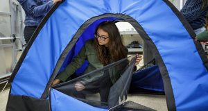 Teenage Girls prepare Solar-Powered Tent for displaced person